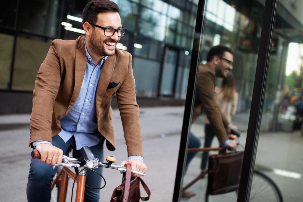 Junger Mann mit Businesskleidung strahlend auf einem Fahrrad