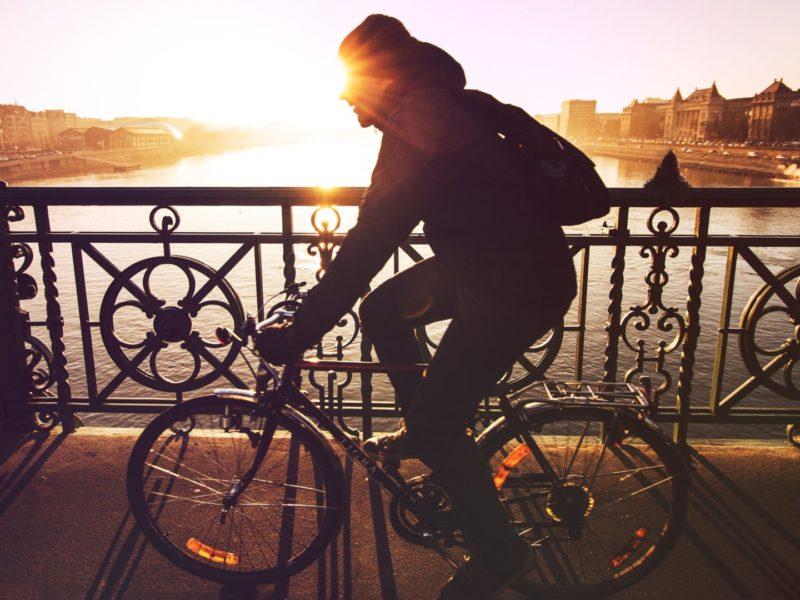 Mann fährt im Sonnenuntergang mit dem Fahrrad