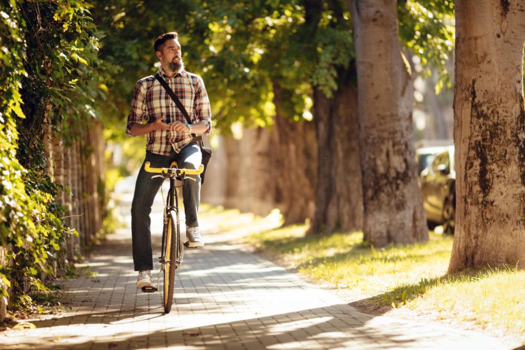 Mann mit Hemd fährt Fahrrad bei Sonnenschein