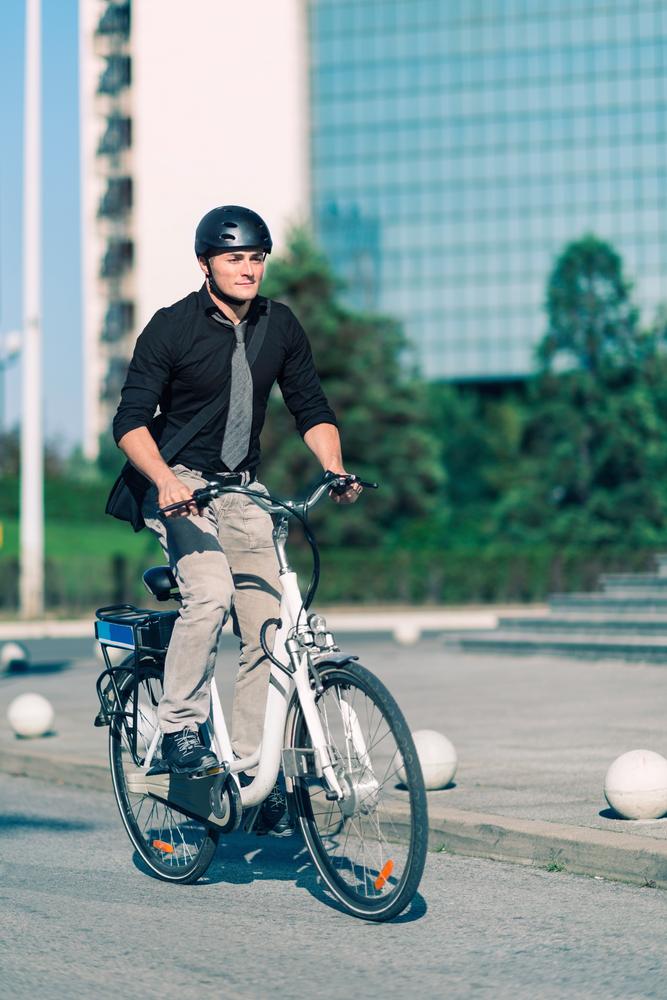 Mann mit Helm, Hemd und Krawatte auf einem ebike