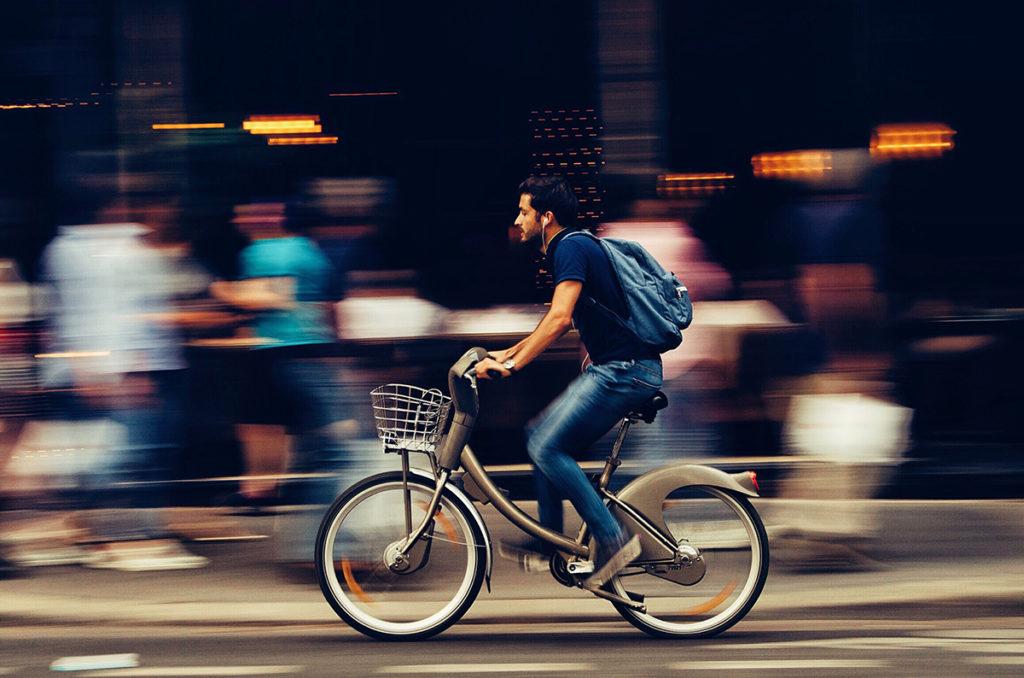 Mann fährt schnell auf einem Fahrrad vor einer Menschenmenge