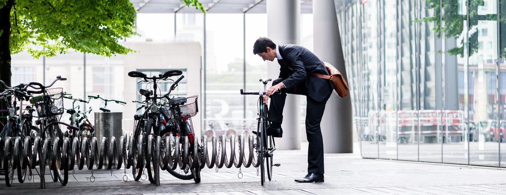 Mann im Anzug schließt sein Fahrrad an.