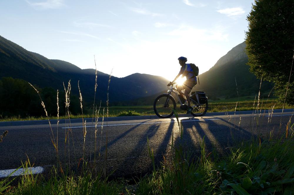 Radfahrer fährt im Abendlicht in der Natur