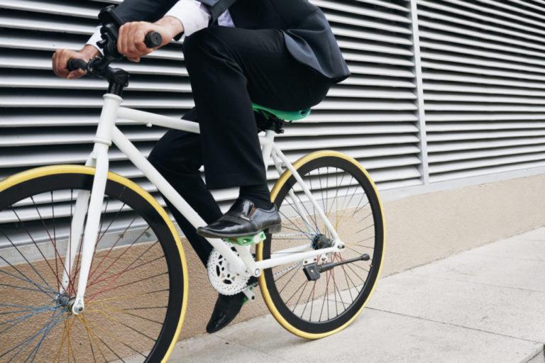 Weißes Fahrrad mit gelben Rädern und einem fahrenden Business-Mann