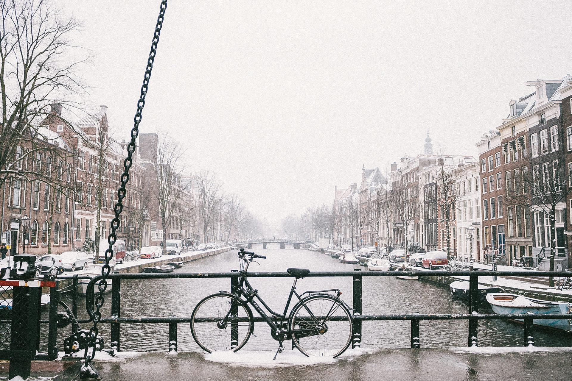 Fahrrad im Schnee an einer Brücke stehend