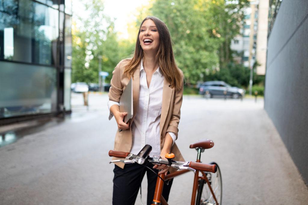 Geschäftsfrau mit Laptop und Fahrrad auf einer Straße in der Stadt