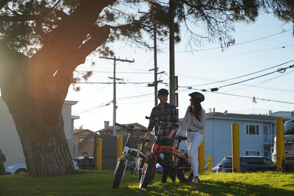 Paar mit E-Bikes im Abendlicht unter einem Baum