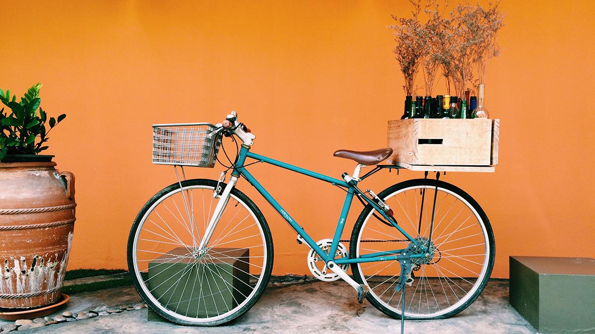 Fahrrad vor orangener Wand mit Fahrradkorb