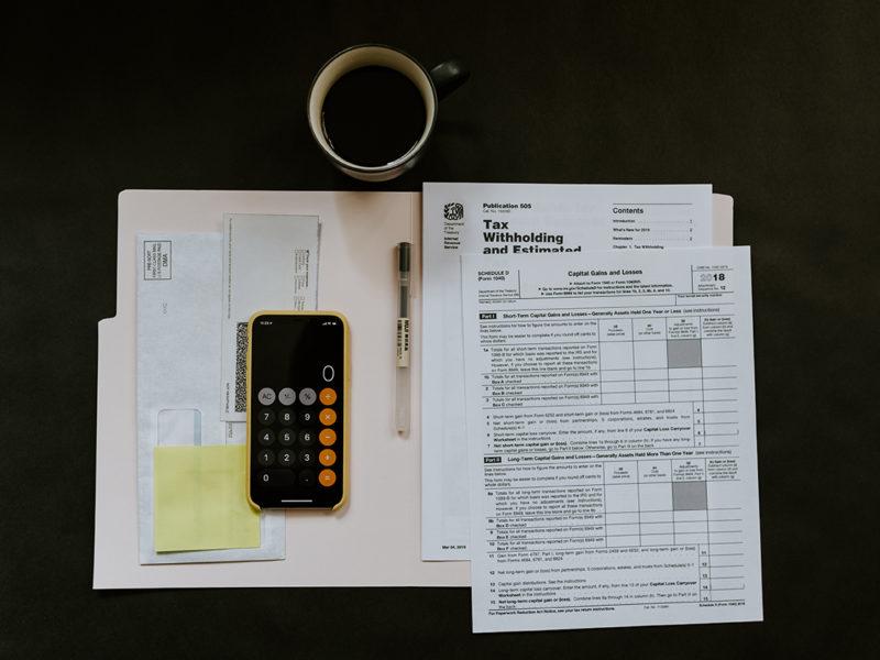 Taschenrechner mit weiteren Unterlagen auf schwarzem Untergrund
