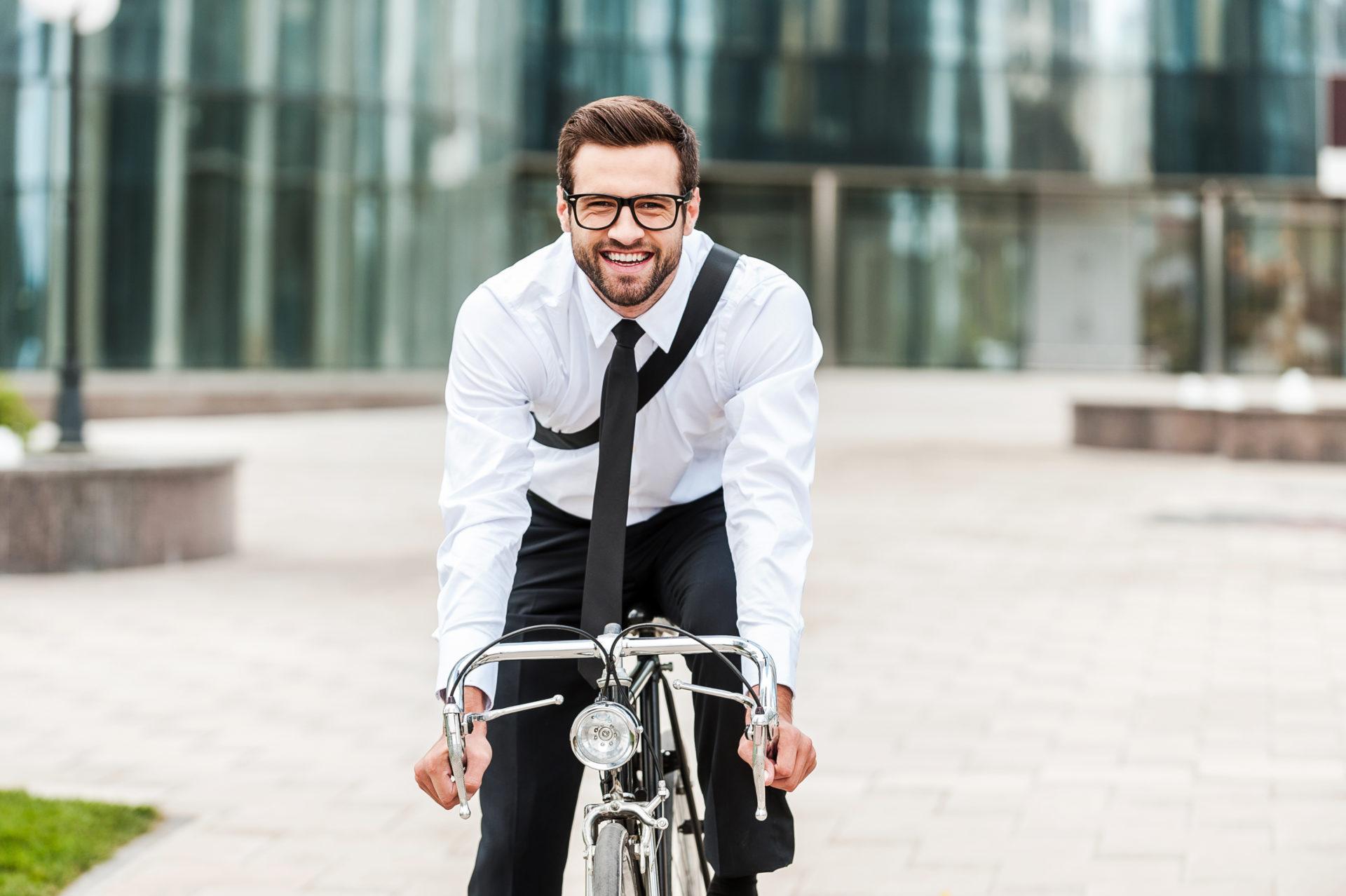 Fröhlicher Mann mit Anzug auf einem Fahrrad