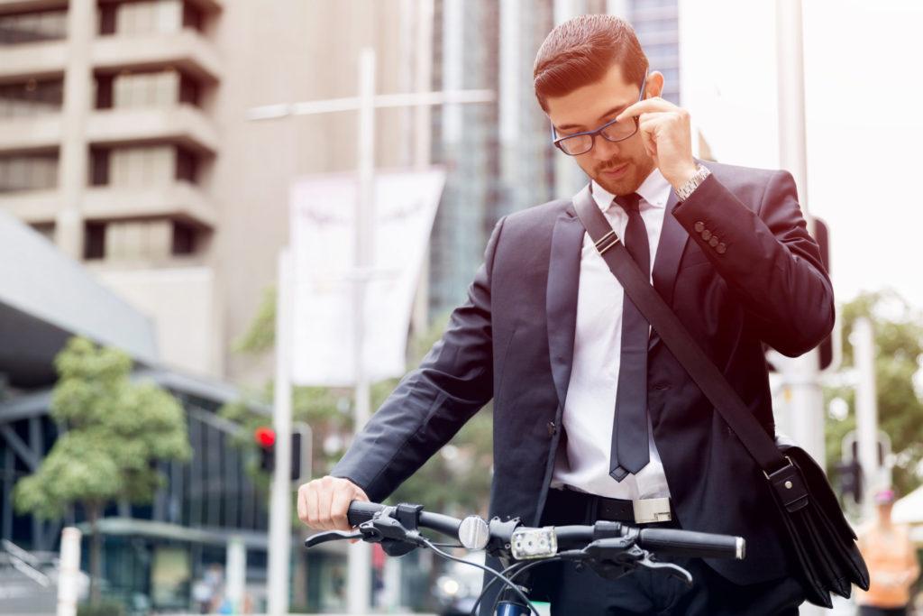 Geschäftsmann mit Brille schiebt sein Fahrrad