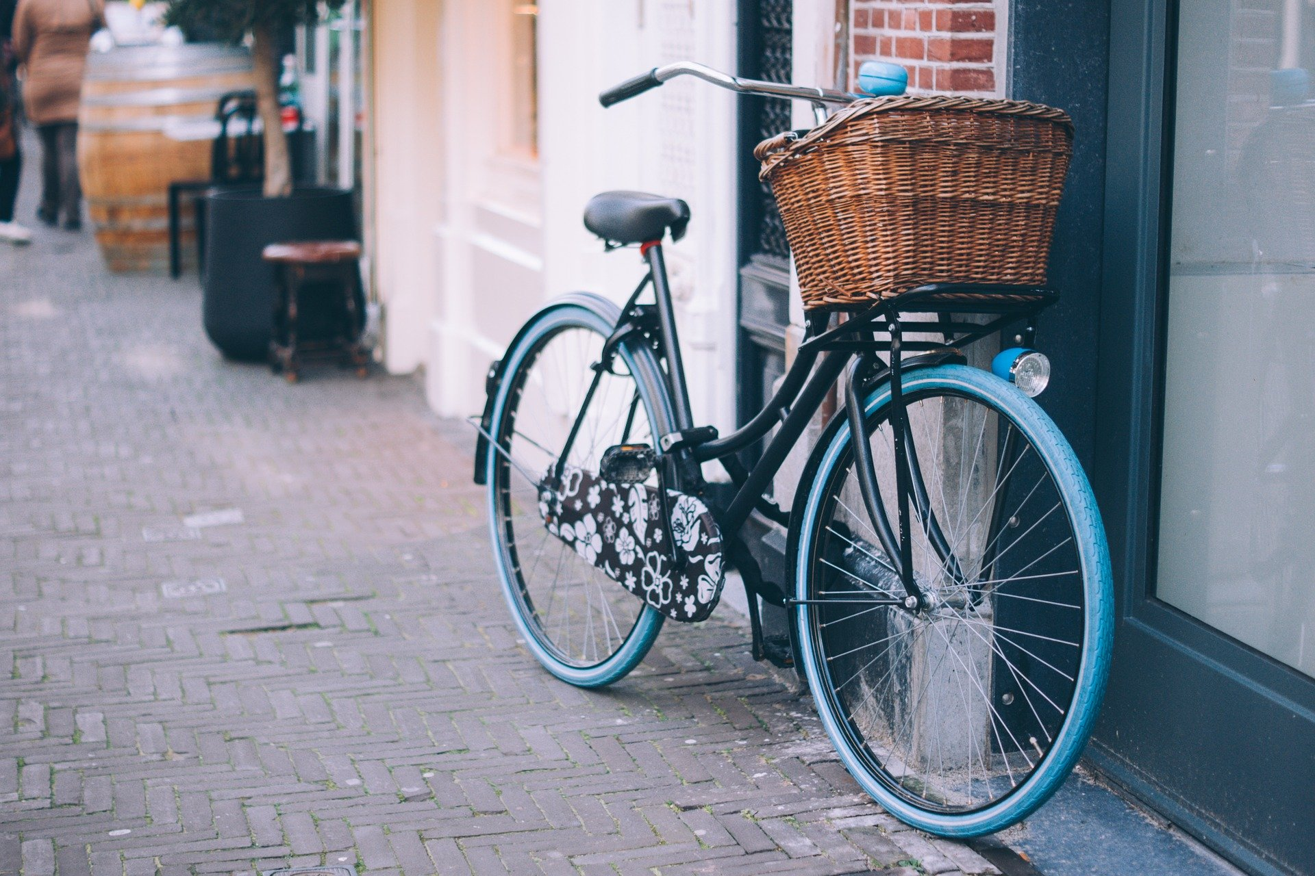 Fahrrad mit blauen Reifen und einem Korb steht an einer Hauswand