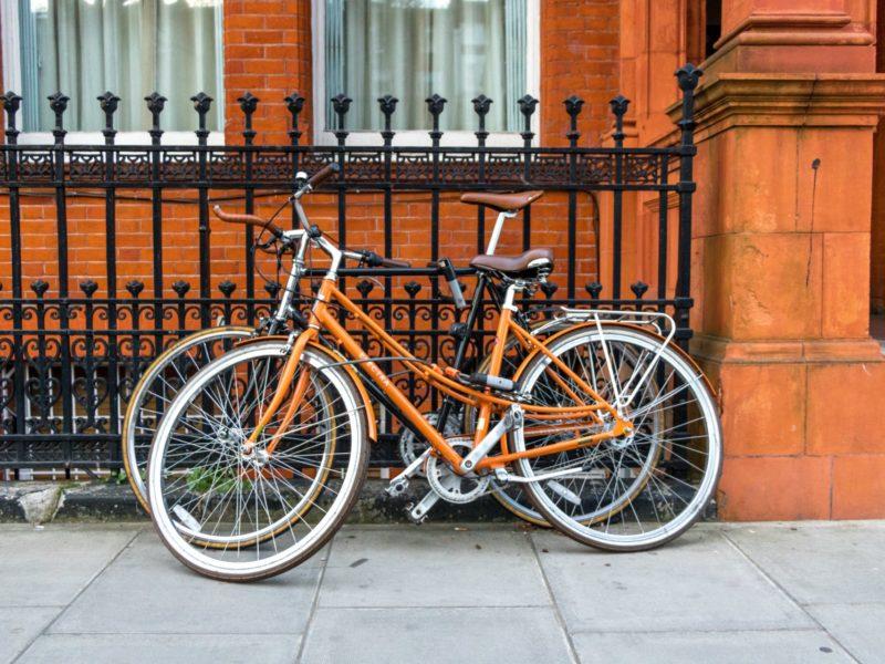Zwei Fahrräder unterschiedlicher Größe lehnen an einem Zaun